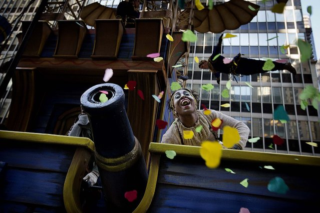 A performer on the Cirque du Soleil float cheers after firing confetti into the crowd on Sixth Avenue. (Photo by John Minchillo/Associated Press)