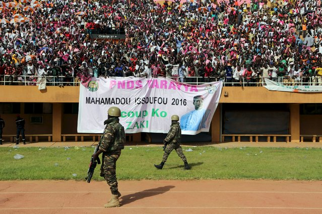 Soldiers walk past a cheering crowd at a campaign rally for incumbent President Mahamadou Issoufou in Niamey, Niger, February 18, 2016. Niger holds presidential and legislative elections on Sunday. (Photo by Joe Penney/Reuters)