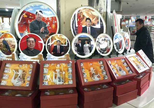 In this photo taken Friday, December 30, 2016, a Chinese man walks past ceramic plates with images of Chinese President Xi Jinping displayed at a rest stop near Beijing. During his annual New Year Eve's speech, Chinese President Xi Jinping says his government will continue to focus on poverty alleviation at home and resolutely defending China's territorial rights on the foreign front. (Photo by Ng Han Guan/AP Photo)