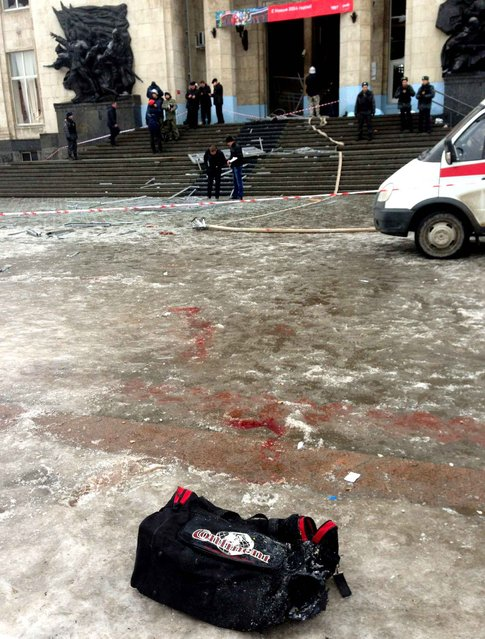 A bag lies on the ground as Russian security personnel inspect the damage at a train station following a suicide attack in the Volga River city of Volgograd, about 900 kms (560 miles) southeast of Moscow, on December 29, 2013. (Photo by AFP Photo/Stringer)