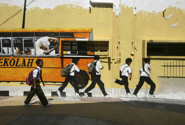A school boy walks past a street mural depicting a school bus and students in Shah Alam, outside Kuala Lumpur January 2, 2014. Malaysia begins the first day of the new school year of 2014 on January 2. (Photo by Samsul Said/Reuters)
