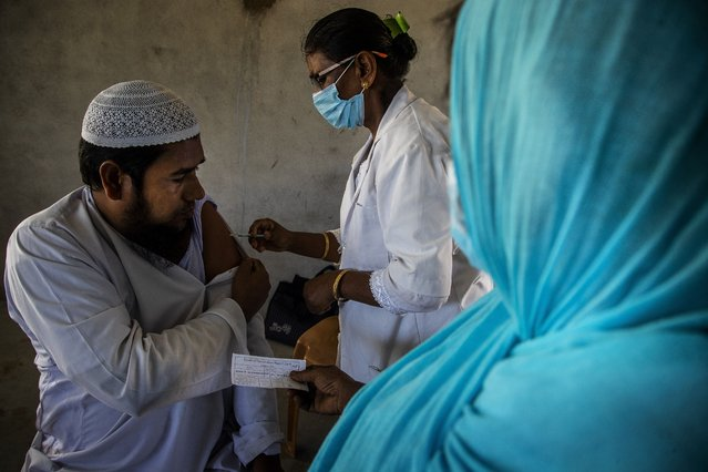 A health worker administers the vaccine for COVID-19 in Khola Bhuyan village on the outskirts of Gauhati, India, Tuesday, September 7, 2021. (Photo by Anupam Nath/AP Photo)
