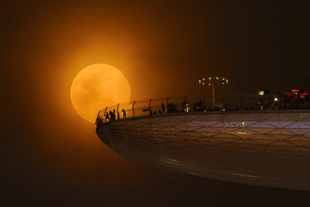 "On June 23, the full moon loomed over skywatchers as a ""supermoon"". This occurs when the moon is the closest it will be to the Earth in the calendar year. The lunar orb appeared 8 percent larger and 17 percent brighter than usual, drawing the eyes, and camera lenses, of readers around the world. Cheng Kiang Ng submitted this supermoon photograph, taken in Marina Bay Sands Skypark in Singapore, to the online Your Shot community on June 24. (Photo by Cheng Kiang Ng/National Geographic)"