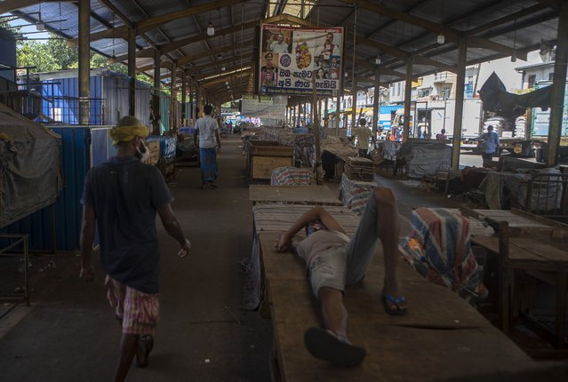 Workers rest at a wholesale market closed to curb the spread of the coronavirus in Colombo, Sri Lanka on  June 16, 2021. (Photo by Eranga Jayawardena/AP Photo)