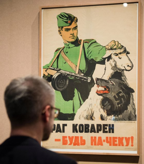 "A man looks at a Soviet poster, dated 1945, that reads ""The enemy is cunning – be on guard!"", part of the exhibition ""1945 – Defeat. Liberation. New Beginning"" at the German Historical Museum in Berlin, Germany, 22 April 2015. The exhibition runs from 24 April until 25 October 2015. (Photo by Gregor Fischer/EPA)"