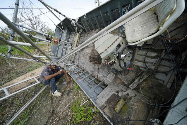 Mike Gaines, a deckhand, sits on the overturned and destroyed shrimp trawler that provides his living, in the aftermath of Hurricane Ida in Plaquemines Parish, La., Monday, September 13, 2021. (Photo by Gerald Herbert/AP Photo)