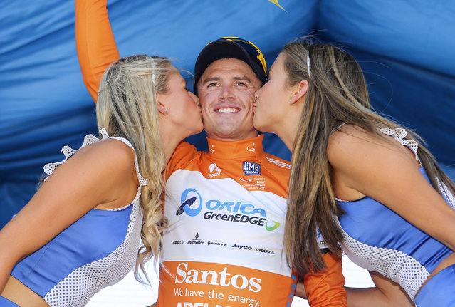 Simon Gerrans (C) of Australia receives a kiss on the podium after being presented the leader's jersey after stage one of the Tour Down Under in Adelaide on January 21, 2014. (Photo by Mark Gunter /AFP Photo)