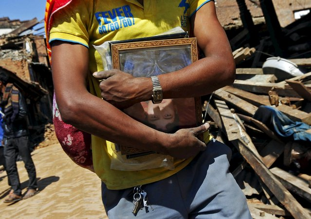 A man carries a framed portrait of a relative, which he recovered from the rubble of his house, following Saturday's earthquake in Bhaktapur, Nepal April 27, 2015. (Photo by Adnan Abidi/Reuters)