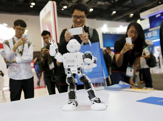 Visitors take pictures of humanoid intelligent robot Alpha developed by UBTECH at the Global Mobile Internet Conference (GMIC) 2015 in Beijing, China, April 28, 2015. (Photo by Kim Kyung-Hoon/Reuters)