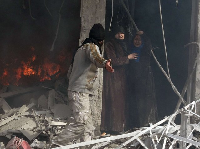 """A man shows the way to two Syrian women as they leave a building following an alleged air strike by Syrian government forces on January 30, 2014 in the northern Syrian city of Aleppo. Syria's government has razed thousands of homes as """"collective punishment"""" of communities that back the opposition in the capital Damascus and in Hama province, Human Rights Watch said. (Photo by Mohammed Al-Khatieb/AFP Photo)"""