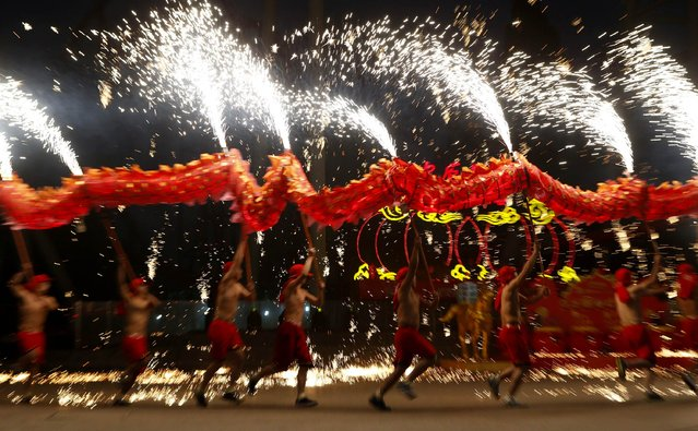 Dancers perform a fire dragon dance in the shower of molten iron spewing firework-like sparks during a folk art performance to celebrate traditional Chinese Spring Festival on the first day of the Chinese Lunar New Year, which welcomes the Year of the Horse, at the Happy Valley amusement park in Beijing January 31, 2014. (Photo by Kim Kyung-Hoon/Reuters)