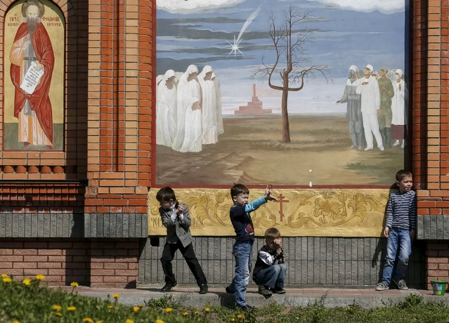 Children play in front of a church at the memorial for victims of the Chernobyl nuclear disaster in Kiev April 26, 2015. (Photo by Gleb Garanich/Reuters)