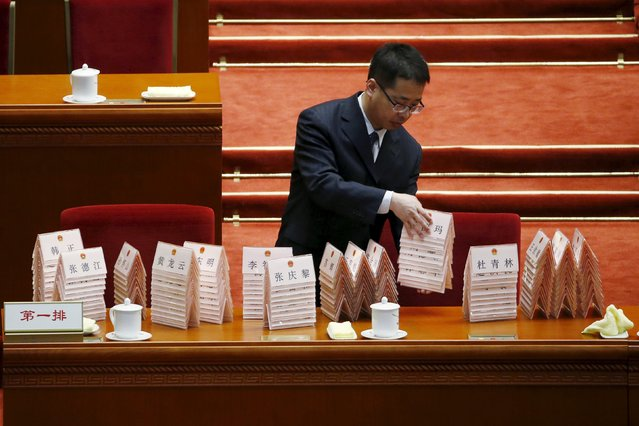 An attendant collects name plates after the third plenary session of the National People's Congress (NPC) at the Great Hall of the People, in Beijing, China, March 13, 2016. (Photo by Kim Kyung-hoon/Reuters)