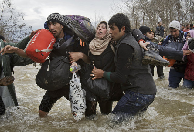 A woman is supported by two men while crossing a river, north of Idomeni, Greece, as migrants attempt to reach Macedonia on a route that would bypass the border fence, Monday, March 14, 2016. (Photo by Vadim Ghirda/AP Photo)