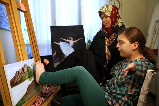 In this picture taken on Wednesday, January 21, 2015, Zohreh Etezadossaltaneh, who was born without arms, teaches painting to 12-year old Sara Sahraei, who is disabled, at her home, in Tehran, Iran. (Photo by Ebrahim Noroozi/AP Photo)