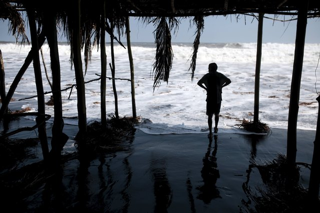 A man looks on as waves damage tourist huts at El Majahual beach in La Libertad May 3, 2015. (Photo by Jose Cabezas/Reuters)