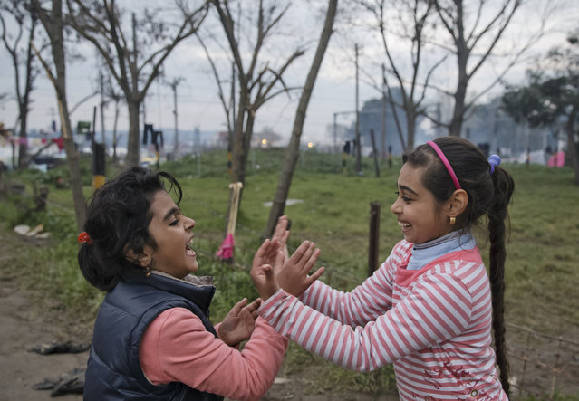 Girls play in the makeshift refugee camp at the northern Greek border point of Idomeni, Greece, Thursday, March 17, 2016. Leaders of the EU's 28 divided nations reconvene in Brussels in hopes of ironing out disagreements on a proposed agreement with Turkey in the migrants crisis. (Photo by Vadim Ghirda/AP Photo)