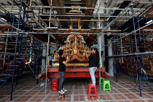 "Thai officials from the Conservation Science Division of the Fine Arts Department of the National Museum of Thailand repairs the Minor Chariot, which will be used during the late King  Bhumibol Adulyadej's funeral later this year, Thailand, February 6, 2017. Inch by gilded inch, the chariot to take Thailand's late king on his last journey is being restored by workers in Bangkok in a labor that will last months. Built of wood and decorated with gold and mirrors, the 13.7 tonne chariot is 18 meters (yards) long, 11.2 meters high and 4.8 meters wide. Pulled by 216 men, it will carry the ornate urn containing King Bhumibol Adulyadej's body to the site of the cremation at the Sanam Luang ground outside the Royal Palace. The king died on Oct. 13 after seven decades on the throne, plunging Thailand into mourning, which for many Thais will last a year. No date has yet been set for the cremation, but it will not take place before October. Known as the ""Great Victory"" Chariot, the vehicle is believed take the divine back to heaven. Renovation began in January and is due to be completed by September. The chariot was first built in 1795 in the time of King Rama I for the cremation of his father. King Bhumibol was Rama IX in the Chakri dynasty. He has been succeeded by his son, King Maha Vajiralongkorn Bodindradebayavarangkun, known as Rama X. The chariot has been used 25 times, most recently in 2012 for the cremation of Princess Bejaratana Rajasuda, the late king's cousin. (Photo by Chaiwat Subprasom/Reuters)"