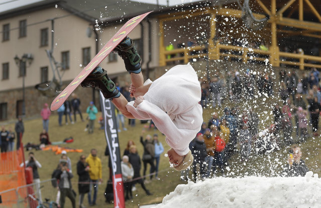 "A Belarusian snowboarder takes part in the comic competition ""Californication 9.0"" at an entertainment center in the town of Logoisk, 40 km (25 miles) north of Minsk, Belarus, Sunday, April 7, 2019. Eighty participants in the costumes skied from the springboard and jumped into the icy water celebrating the end of winter. (Photo by Sergei Grits/AP Photo)"