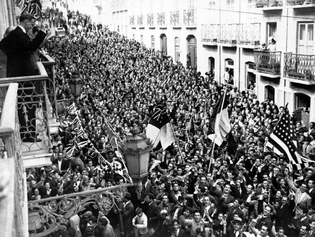 People crowd into the street outside the U.S. and British Embassies, Lisbon, Portugal, on VE Day, May 8, 1945. Jubilant crowds celebrated for two days and nights. (Photo by AP Photo)