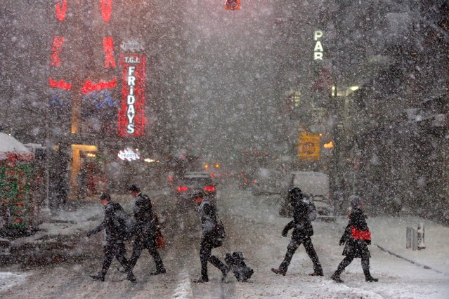 Pedestrians walk in Times Square as snow falls in Manhattan, New York, U.S. February 9, 2017. (Photo by Andrew Kelly/Reuters)