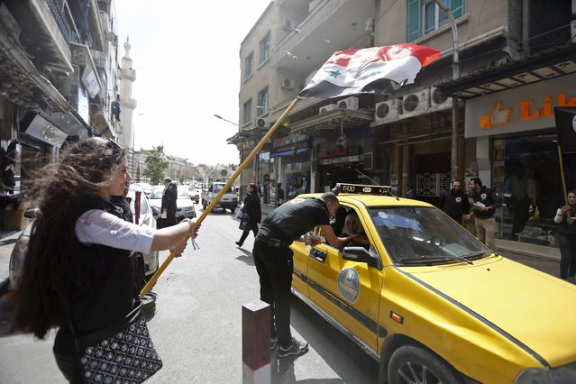 A girl holds a Syrian national flag as a supporter of the Syrian Social Nationalist party offers traditional arabic sweets to celebrate Syrian Mother's Day in the ancient Christian quarter of Bab-Touma in Damascus, Syria March 21, 2016. (Photo by Omar Sanadiki/Reuters)