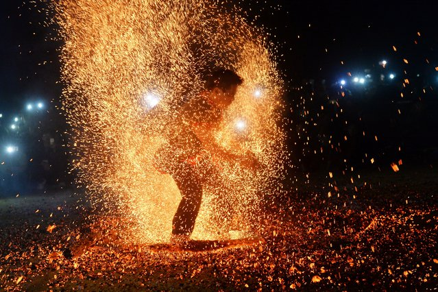 This picture taken on February 10, 2017 shows a Pa Then ethnic dancer removing burning ashes during a fire dance at a local spring festival in Lam Binh district, northern province of Tuyen Quang. Deep in trance, the lithe young men prance on piles of glowing embers, careful not to sear their feet at the ritual fire dance to exorcise spiritual demons and pray for a healthy harvest. Once dismissed as superstitious and banned by Vietnam's communist authorities, the Pa Then ethnic minority now perform the fire dance publicly after decades of celebrating in the woods in secret. (Photo by Hoang Dinh Nam/AFP Photo)