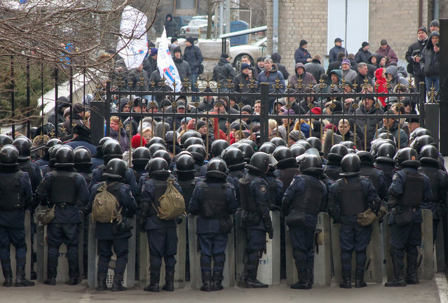 Riot police stand in line in front of pro-Russian protesters, who try to occupy the Regional administration building in Donetsk, Ukraine, 03 March 2014. According to reports, pro-Russian demonstrators managed to occupy parts of the administration building in the home town of toppled Ukrainian president Viktor Yanukovych. (Photo by EPA/Photomig)