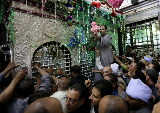 In this photo taken Tuesday, May 12, 2015, an Egyptian decorates the shrine of Sayyeda Zeinab with flowers, as hundreds celebrates a religious festival, or Moulid, which commemorates of the birth of Muslim Prophet Muhammad's granddaughter Sayyeda Zeinab, inside the mosque and shrine named for her, in Cairo, Egypt. (Photo by Amr Nabil/AP Photo)