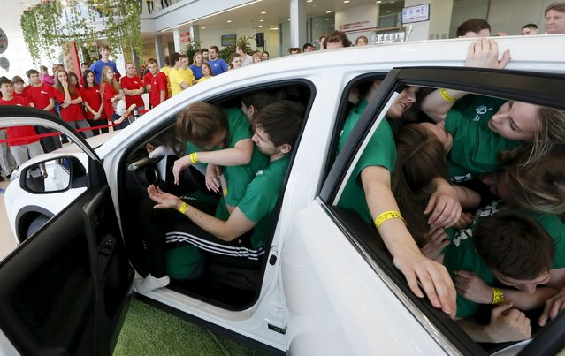 Students from the Siberian State Aerospace University team squeeze into a car during a local competition and attempt for a Guinness Book of World Records for the most number of people in a car in Krasnoyarsk, Russia, May 16. 2015. (Photo by Ilya Naymushin/Reuters)