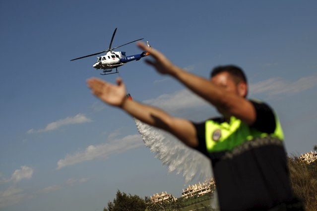 A helicopter drops water over a wildfire as a local police officer directs traffic on a road in Benahavis, southern Spain, May 19, 2015. (Photo by Jon Nazca/Reuters)