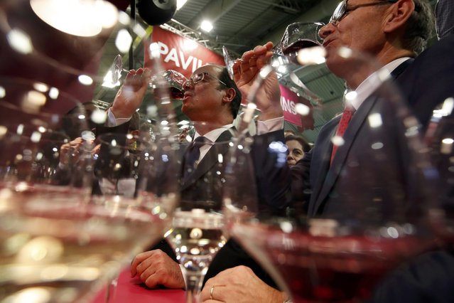 French President Francois Hollande (L) drinks a glass of wine as he visits the International Agricultural Show in Paris, France, February 25, 2017. The Paris Farm Show runs from February 25 to March 5, 2017. (Photo by Christian Hartmann/Reuters)