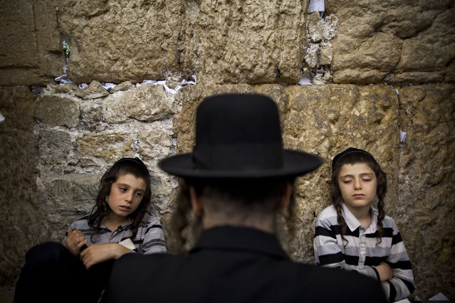 Ultra-orthodox Jewish men pray as they gather for the mourning ritual of Tisha B'Av at the Western Wall, the holiest site where Jews can pray, in Jerusalem's Old City, early Sunday, July 29, 2012. (Photo by Oded Balilty/AP Photo)