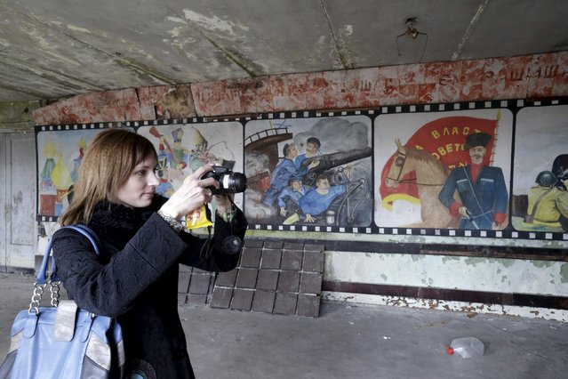 A woman takes a picture inside Soviet propaganda room in the ghost town of a former Soviet military radar station near Skrunda, Latvia, April 9, 2016. (Photo by Ints Kalnins/Reuters)