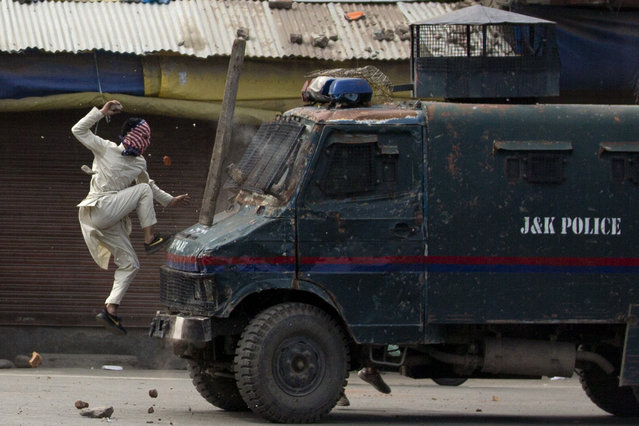A masked Kashmiri protester jumps on the bonnet of an armored vehicle of Indian police as he throw stones at it during a protest in Srinagar, Indian controlled Kashmir, Friday, May 31, 2019. Government forces in Indian controlled Kashmir fired tear gas and pellets to disperse hundreds of protesters who clashed with them during a protest against the recent killing of Kashmir rebel leader and also an annual protest marking Al-Quds Day. The last Friday of the Islamic holy month of Ramadan is observed in many Muslim communities as Al-Quds Day, or Jerusalem Day, as a way of expressing support to the Palestinians and emphasizing the importance of Jerusalem to Muslims. (Photo by Dar Yasin/AP Photo)