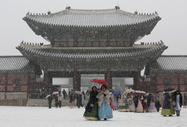 In this Thursday, December 13, 2018, file photo, visitors huddle under umbrellas in the snow at the Gyeongbok Palace, the main royal palace during the Joseon Dynasty, and one of South Korea's well known landmarks in Seoul, South Korea. (Photo by Ahn Young-joon/AP Photo)