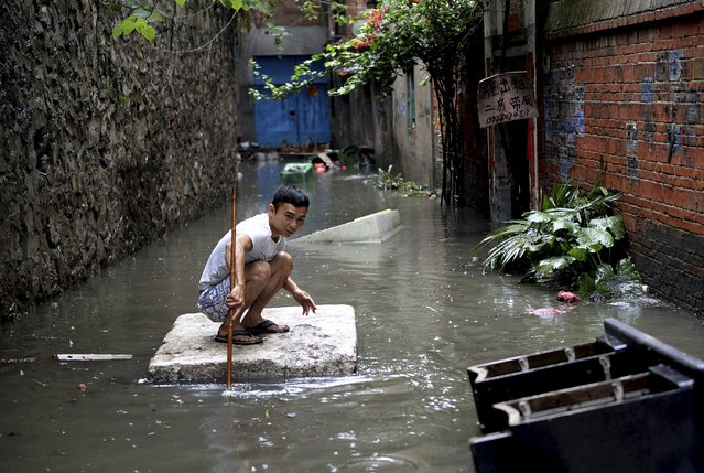 A man travels down a flooded alley on a styrofoam board following heavy rainfall in Liuzhou, Guangxi Zhuang Autonomous Region, China, May 20, 2015. (Photo by Reuters/China Daily)