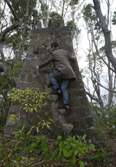 The image made available on 31 March 2014 shows a tourist climbing an abandoned whale watch tower in Taiji city, Wakayama prefecture, Japan, 29 March 2014. (Photo by Everett Kennedy Brown/EPA)