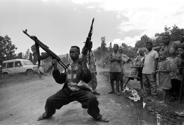 A Mai-Mai rebel soldier shows off his guns at a checkpoint near the Mugunga refugee camp in Zaire; 1996. (Photo by Carol Guzy/The Washington Post)