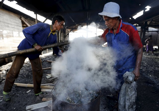 Workers cook a bucket of green mussels at Muara Angke slump area in North Jakarta, Indonesia, April 20, 2016. (Photo by Reuters/Beawiharta)