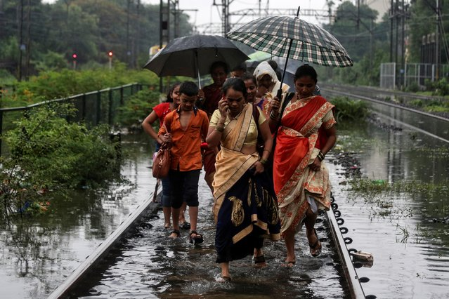 Commuters walk on waterlogged railway tracks after getting off a stalled train during heavy monsoon rains in Mumbai, July 2, 2019. (Photo by Francis Mascarenhas/Reuters)