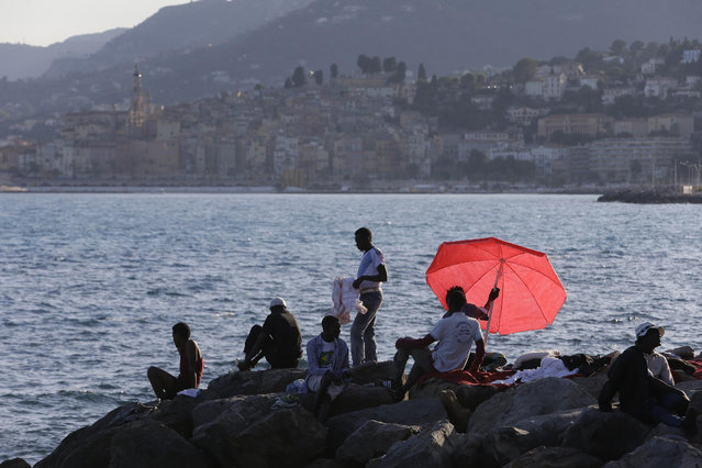 Migrants sit on the rocky beach at the Franco-Italian border in Ventimiglia, Italy, Wednesday, June 17, 2015. European Union nations failed to bridge differences Tuesday over an emergency plan to share the burden of the thousands of refugees crossing the Mediterranean Sea, while on the French-Italian border, police in riot gear forcibly removed dozens of migrants. (AP Photo/Lionel Cironneau)