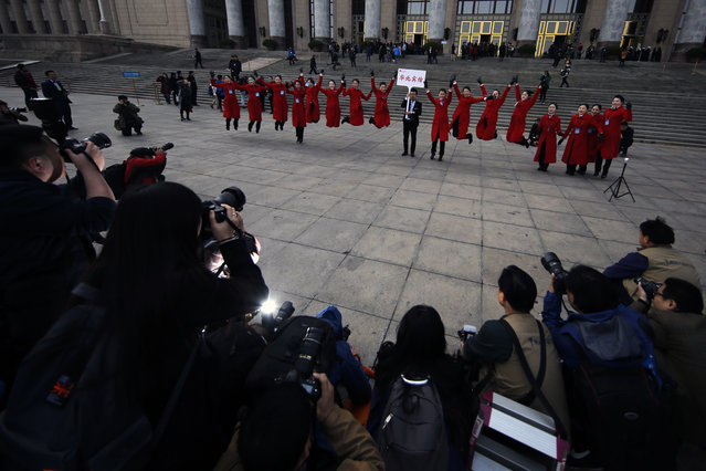 In this Friday, March 3, 2017 photo, hospitality staff jump as they pose for photographs in front of the Great Hall of the People during the Chinese People's Political Consultative Conference (CPPCC) in Beijing. (Photo by Andy Wong/AP Photo)