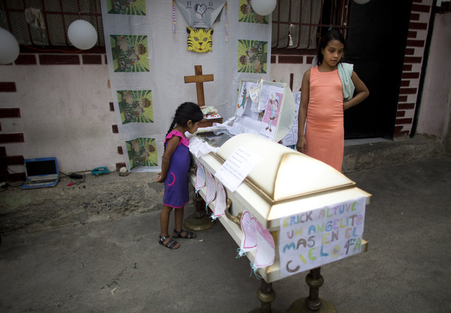 Shara Altuve, 12, right, stands by the coffin of her 11-year-old brother Erick during his wake in a small plaza near their home in the Petare shantytown of Caracas, Venezuela, Wednesday, May 29, 2019. Erick died on May 26 while he was waiting for a bone marrow transplant. The deaths of several Venezuelan children with cancer who were hoping for bone marrow transplants have ignited a bitter dispute between the government and opponents over who is to blame. (Photo by Ariana Cubillos/AP Photo)