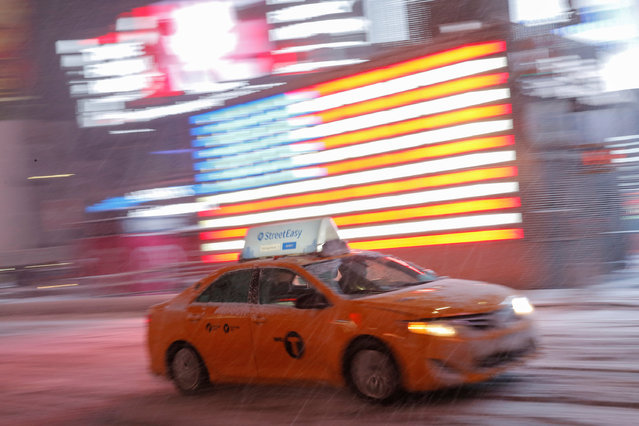 A taxi cab drives through Times Square as snow falls in Manhattan, New York, U.S., March 14, 2017. (Photo by Andrew Kelly/Reuters)