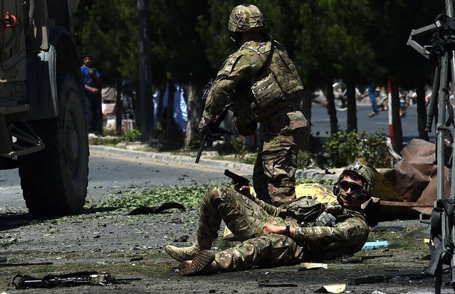 An injured NATO soldier lies on the ground following a suicide car bomb attack that targeted foreign military vehicles in the Afghan capital Kabul on June 30,2015. A powerful blast hit downtown Kabul on June 30 as a suicide car bomber targeted foreign military vehicles, officials said, with casualties feared. (Photo by Wakil Kohsar/AFP Photo)
