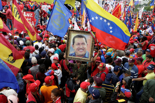 A supporter of Venezuela's President Nicolas Maduro holds a portrait of Venezuela's late President Hugo Chavez, during a rally to commemorate May Day, in Caracas, Venezuela, May 1, 2016. (Photo by Marco Bello/Reuters)