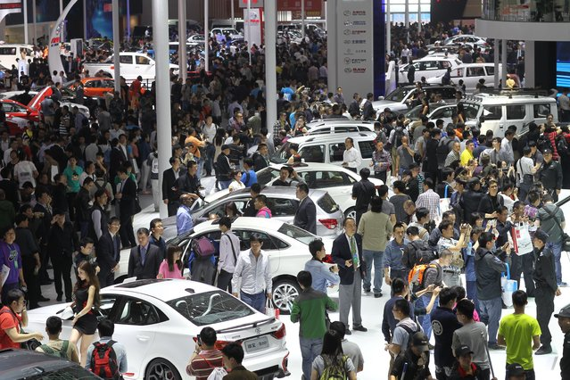 """Visitors gather to look at the cars on display during the """"Auto China 2014"""" Beijing International Automotive Exhibition in Beijing on April 21, 2014. (Photo by AFP Photo)"""