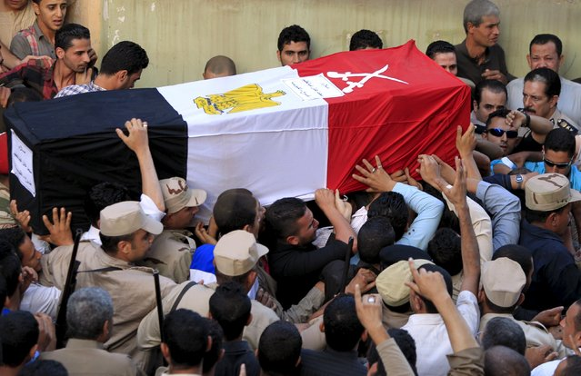 Relatives of 21-year-old Mohamed Adel, one of the army officers who died in yesterday's Sinai attacks, carry his coffin during the funeral in Al-Kaliobeya, near Cairo, Egypt, July 2, 2015. (Photo by Mohamed Abd El Ghany/Reuters)