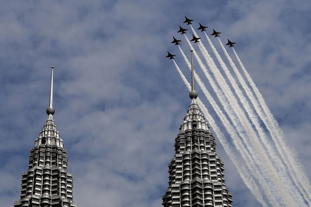"""The South Korean Air Force """"Black Eagles"""" aerobatic team flies past Malaysia's Petronas Twin Towers in Kuala Lumpur on March 29, 2017. (Photo by Manan Vatsyayana/AFP Photo)"""